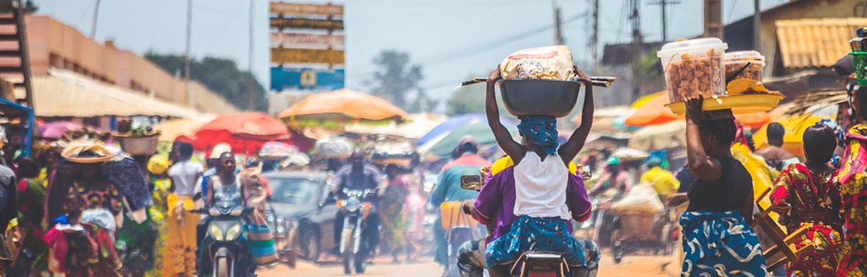 Image of a sub-Saharan African market as a backdrop to women carrying goods on their heads in a traditional way in the foreground