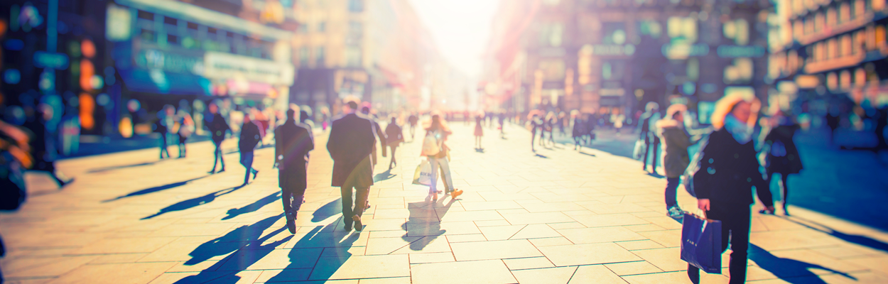 Blurred photograph of people walking on a large city center footpath, with the autumn sun shining through
