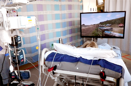 patient in bed using gaming for recovery