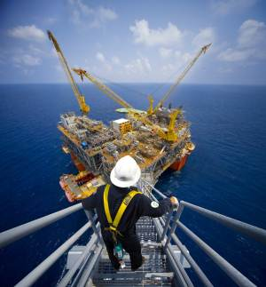 Oil rig worker with oil rig in background - photo courtesy of BP plc.