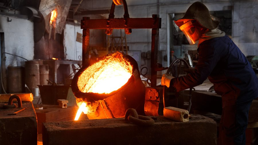 Foundry worker pouring molten metal into a casting