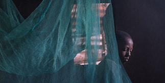 African child behind a mosquito net