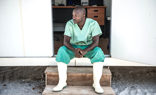 Doctor sits outside mobile laboratory in Guinea during Ebola outbreak.
