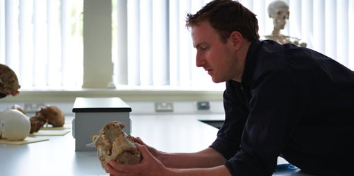 An academic studying a skull