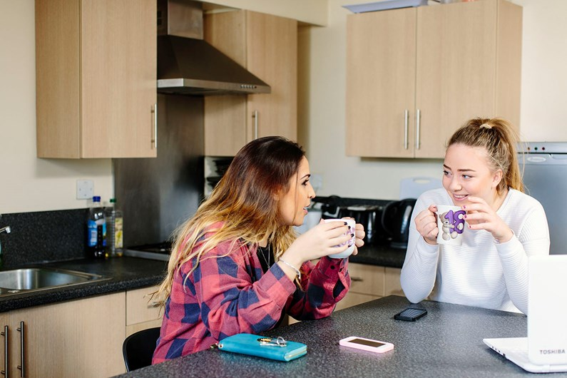 Two girls chatting in the kitchen while drinking hot drinks