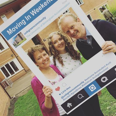 A mother and father with their daughter, holding up an life-sized Instagram frame on moving in day