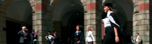 Graduate walking in front of arches