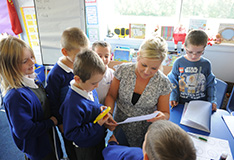 Female teacher talking to primary school pupils