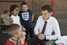 Male teacher talking to primary school pupils