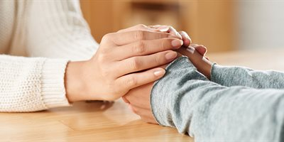 Carer holding hands with patient
