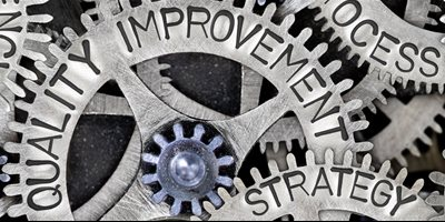 Cogs with words such as quality improvement and strategy on them