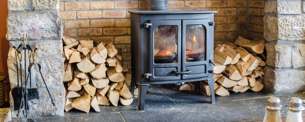 Image of a lit wood burner, set in a fire place.