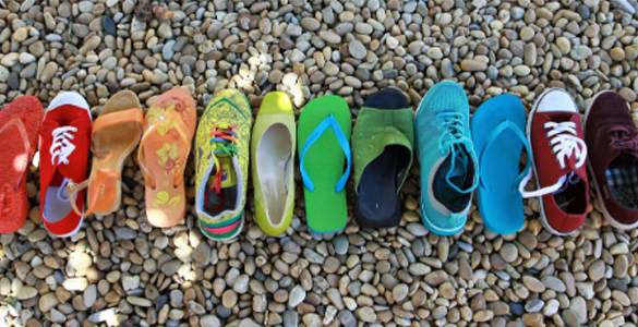 Image of coloured shoes on a beach to illustrate equality