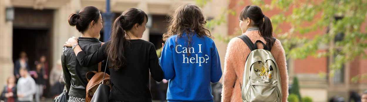 Student ambassador wearing a 'Can I Help?' jumper, walking with three female international students