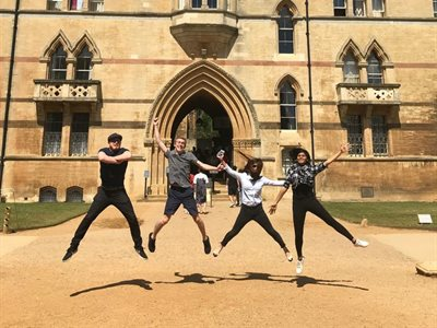 Students jumping in the air outside one of the Oxford Colleges