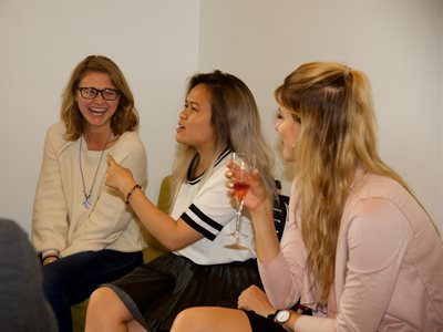 Three students talking and laughing at a drinks reception following the Summer School awards ceremony.