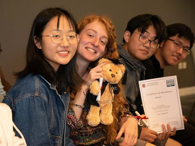 Summer School students at their awards ceremony holding a certificate and a teddy with mini graduation cap and gown