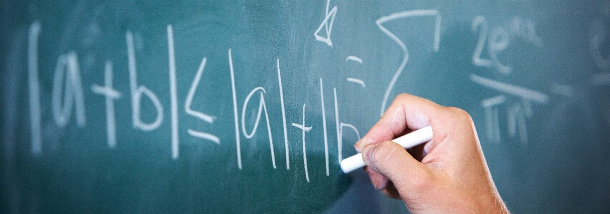 hand writing mathematical symbols on a blackboard