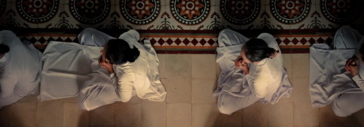 worshippers in white tunics sitting on the floor in prayer