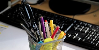 Pot of pens and stationery next to a computer keyboard