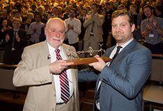 Male chemist handing another male chemist an award