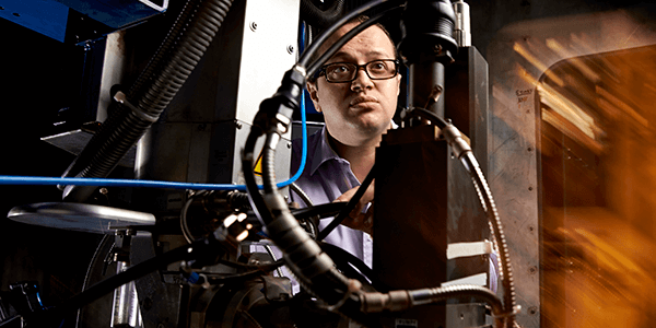 Male manufacturing researcher next to equipment