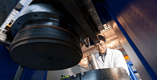 Male manufacturing researcher operating equipment