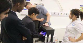 Three university students with a school child using a UV black light