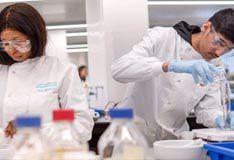 Male and female biomedical students working in a lab