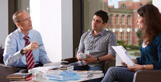A discussion between two men and a woman, sitting around a table in an office