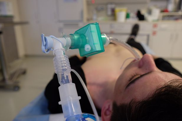 Intubated man lying on a bed in a hospital ward