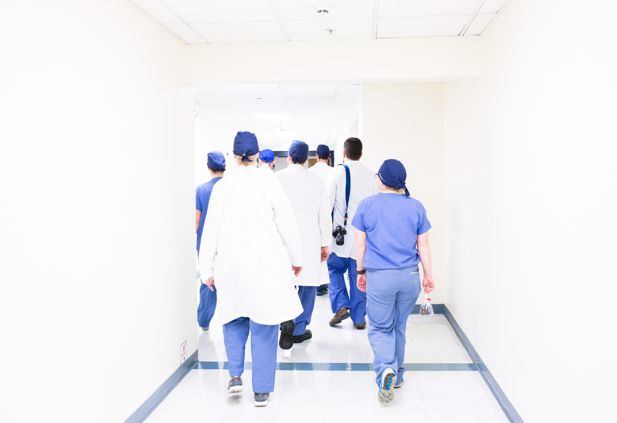 Healthcare workers walking down hospital corridor