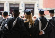 A group of graduates pose together upon graduation.