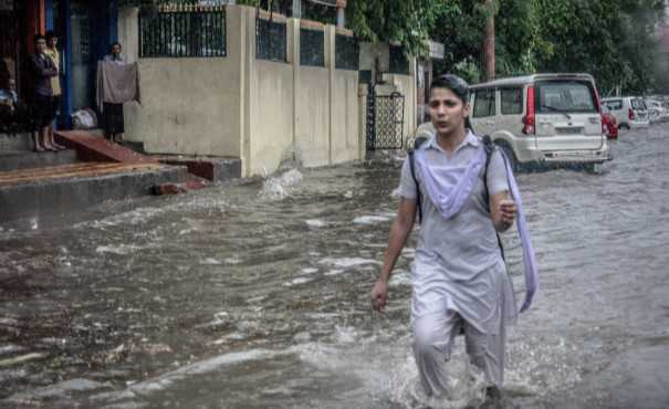 Person walking down a flooded street in India