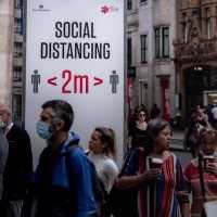 Social distancing sign in busy London shopping district
