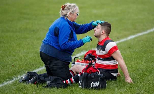 A medic tending to an injured rugby player