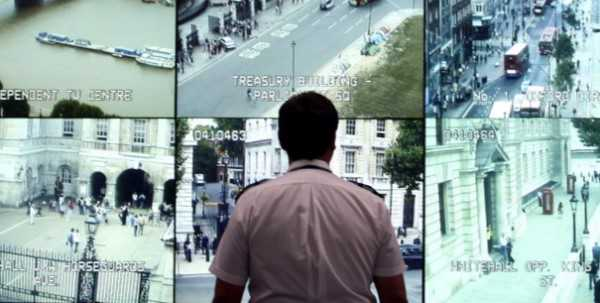 Police Officer overlooking several CCTV screens