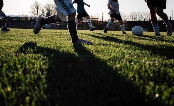 Children playing football on a sports pitch