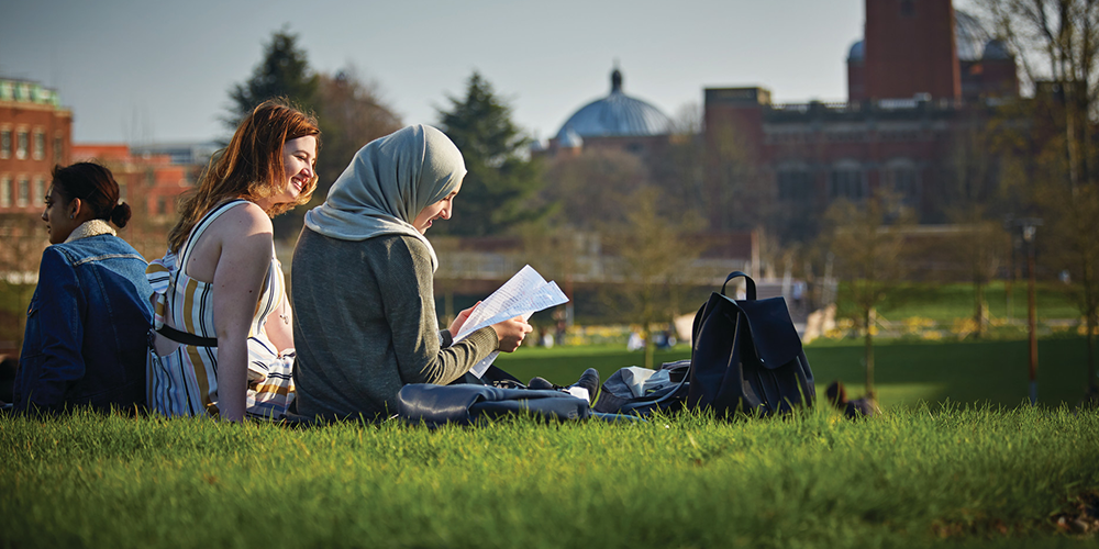 Two students reading on the green heart