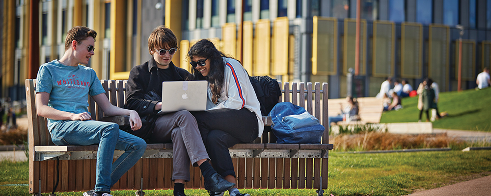 Students gathered around a laptop outdoors on a bench