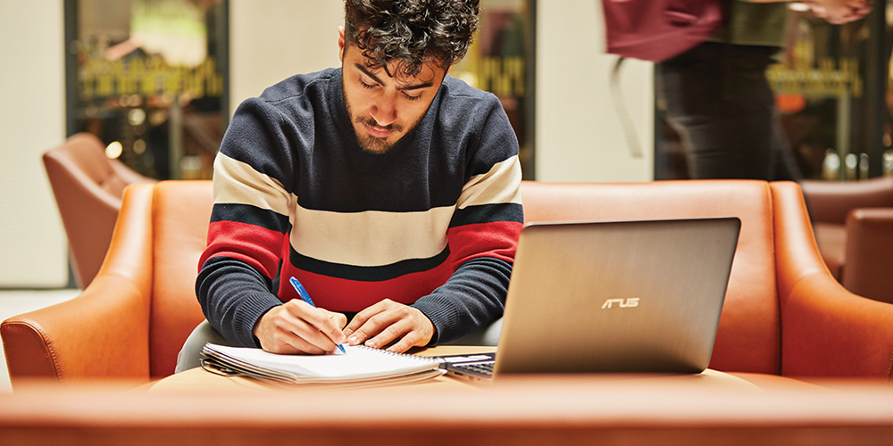 Young man studying in front of laptop