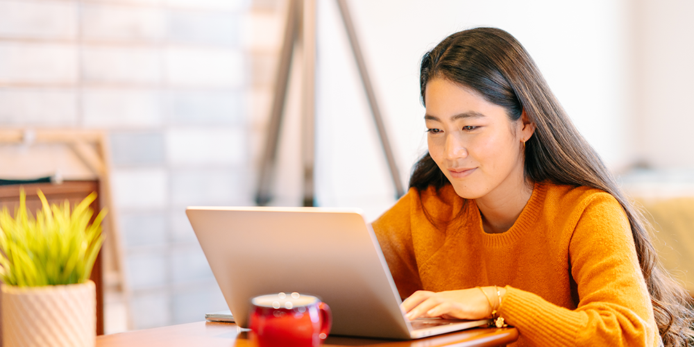 Young woman studying in front of laptop