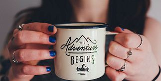 Woman holding mug with words 'Adventure Begins'
