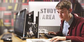 Male student using a computer in front of a sign reading 'Study Area'