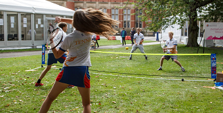 Students playing tennis on campus